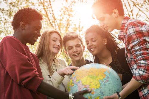 地球儀を囲む若者